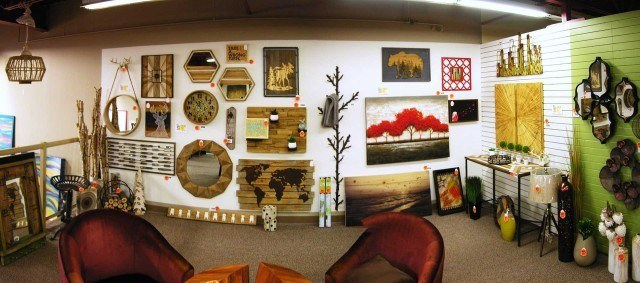 A white wall inside a store with paintings and other decorative wooden items for sale