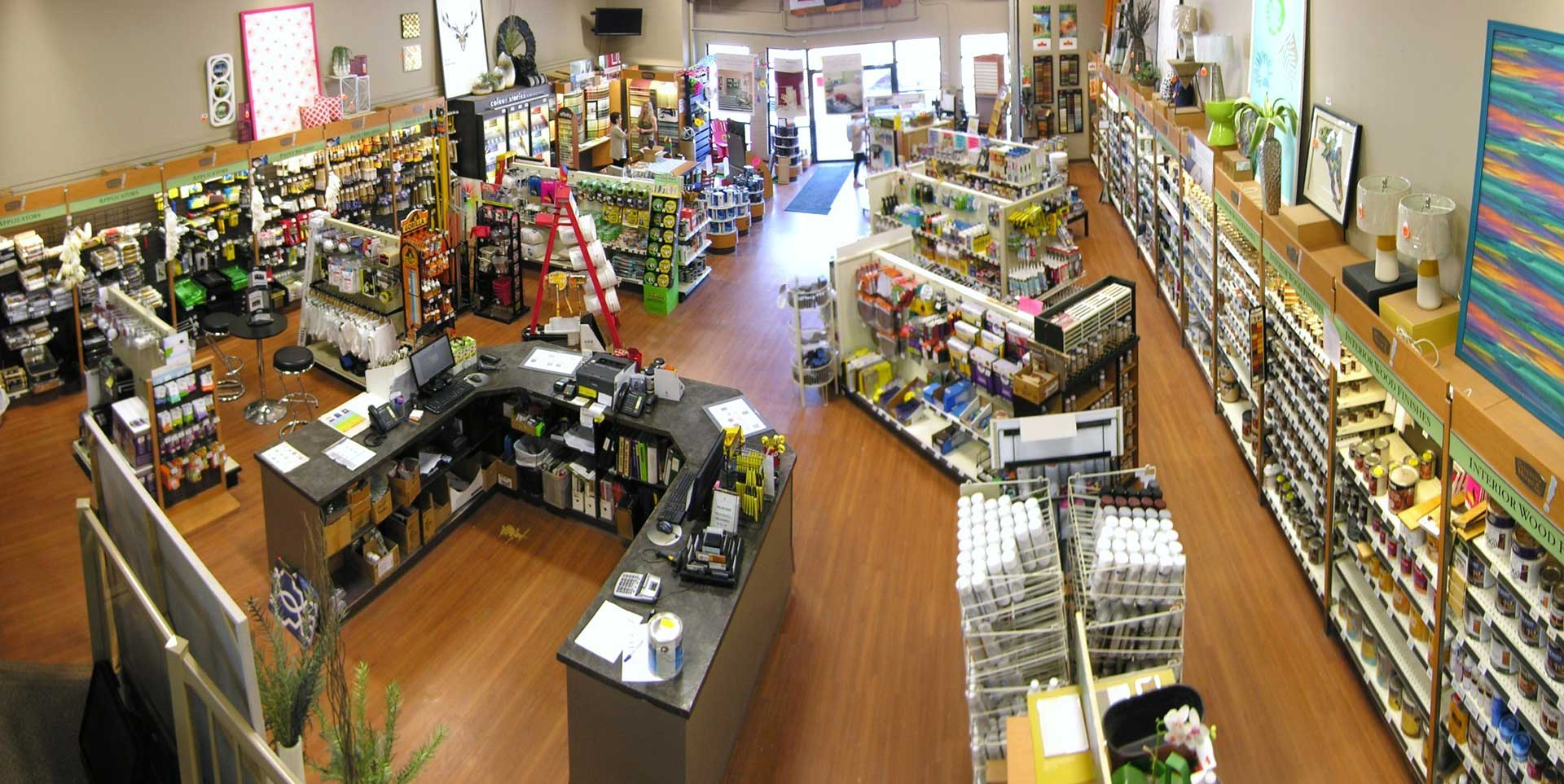 The inside of a paint store with many shelves of paint cans and painting supplies
